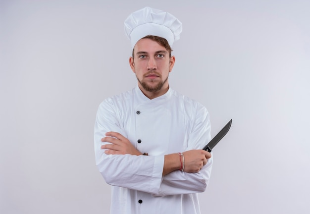 白い壁を見ながらナイフを持っている白い制服を着た真面目な若いひげを生やしたシェフの男