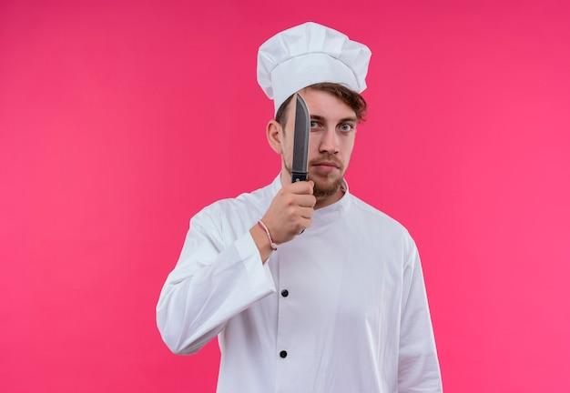 ピンクの壁を見ながら鋭いナイフを持っている白い制服を着た真面目な若いひげを生やしたシェフの男