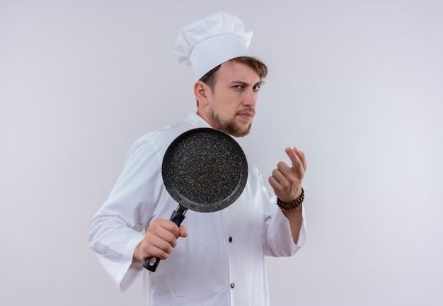 白い壁に野球のバットのようにフライパンを持って白い炊飯器の制服と帽子を身に着けている真面目な若いひげを生やしたシェフの男