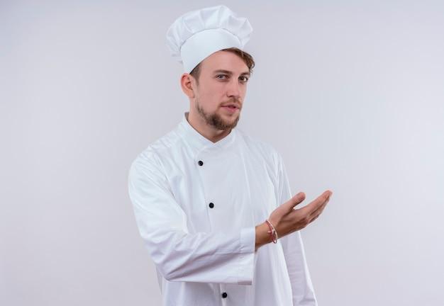 Серьезный молодой бородатый шеф-повар в белой униформе и шляпе, приглашающий подойти с рукой, глядя на белую стену