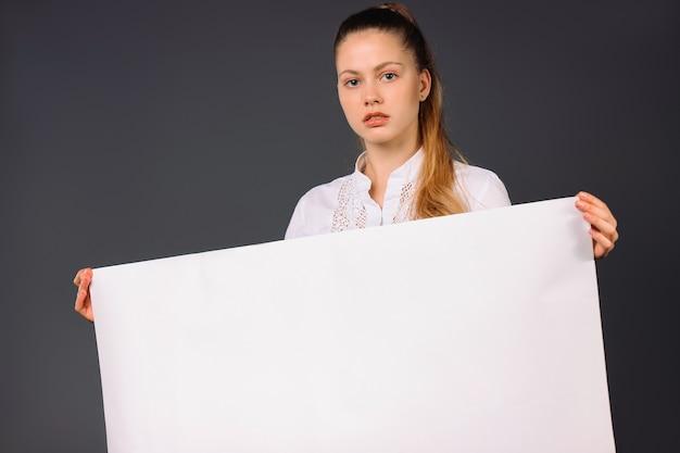 심각한 젊은 비즈니스 우먼 그녀의 팔에 빈 흰색 배너를 보유