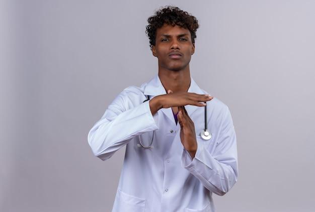 Серьезный молодой красивый темнокожий доктор с вьющимися волосами в белом халате со стетоскопом показывает символ, выражающий просьбу о времени