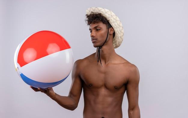 インフレータブルボールを見て太陽の帽子をかぶっている巻き毛を持つ深刻な若いハンサムな浅黒い男