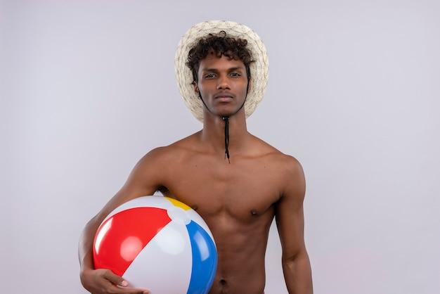 インフレータブルボールを押しながら太陽の帽子をかぶっている巻き毛を持つ深刻な若いハンサムな浅黒い男