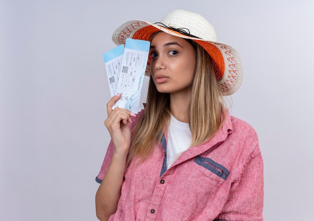 Серьезная молодая женщина в красной рубашке держит билеты на самолет, глядя на белую стену