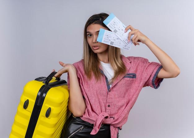 白い壁を見ながら飛行機のチケットと黄色のスーツケースを保持している赤いシャツを着ている深刻な若い女性