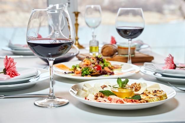 Гостей ждет сервированный столик в ресторане с бокалами красного вина и закусками.