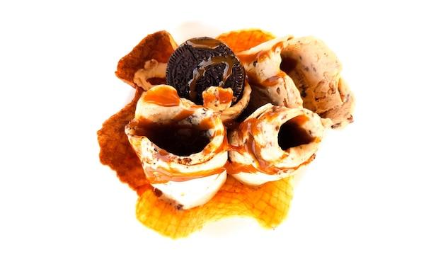 Подача жареного мороженого с карамелизированным банановым кремом печенья в летнем кафе с белым столом.
