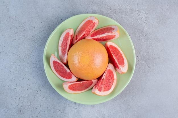 Порция грейпфрута на блюде на мраморном фоне.