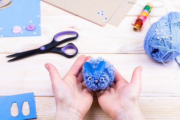 Набор для рукоделия на деревянном столе. нитки, ножницы, бумага для изготовления кролика из помпонов.