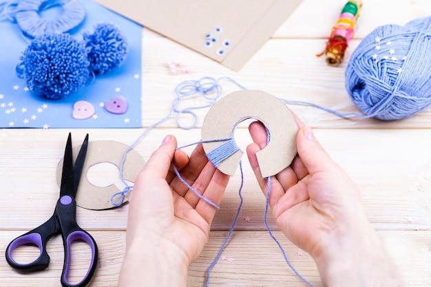 Набор для рукоделия на деревянном столе. нитки, ножницы, бумага для изготовления помпонов.