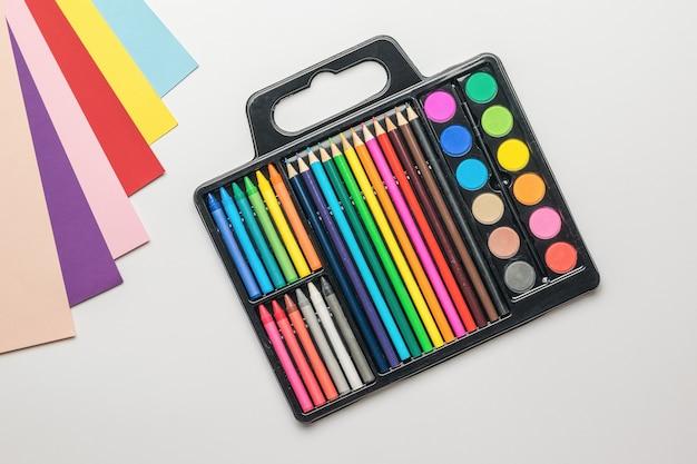 Набор для художника и образцы цветной бумаги на белом фоне. аксессуары для творчества.