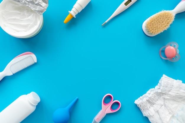 아기 위생, 평면 레이아웃, 위쪽 보기, 텍스트 복사 공간을 위한 액세서리 및 화장품 세트. 파란색 배경에 신생아 관리를위한 위생 제품. 아기 배경.