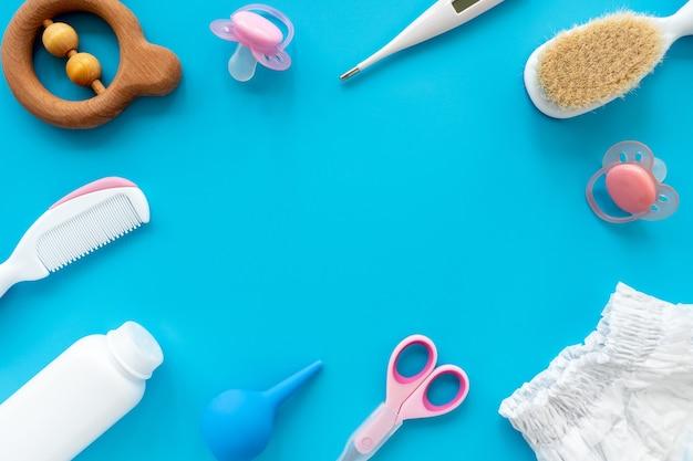 아기 위생, 평면 레이아웃, 위쪽 보기, 텍스트 복사 공간을 위한 액세서리 및 화장품 세트. 파란색 배경에 신생아 관리를 위한 위생 제품. 아기 배경입니다.