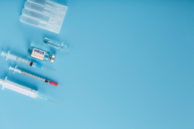 Набор ампул и шприцев с надписью virus vacine и набор шприцев на синем фоне.