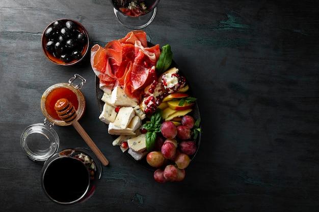 Набор закусок для вина, хамона, пепперони, сыра, винограда, персика и оливок на виде сверху.