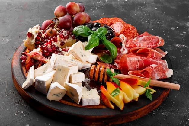 나무 판자에 있는 와인, 자몬, 페퍼로니, 치즈, 포도, 복숭아, 올리브를 위한 전채 세트가 닫혀 있습니다. 어두운 회색 배경에 스낵 보드입니다. 고품질 사진