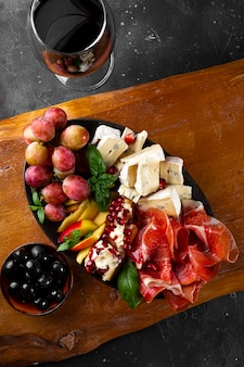 Набор закусок для вина, хамона, пепперони, сыра, винограда, персика и оливок на виде сверху деревянной доски.