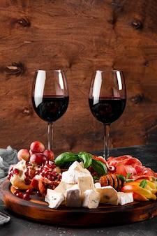 테이블에 와인, 자몬, 페퍼로니, 치즈, 포도, 복숭아, 올리브를 위한 전채 세트. 스낵 보드와 레드 와인 두 잔 세로 사진. 고품질 사진