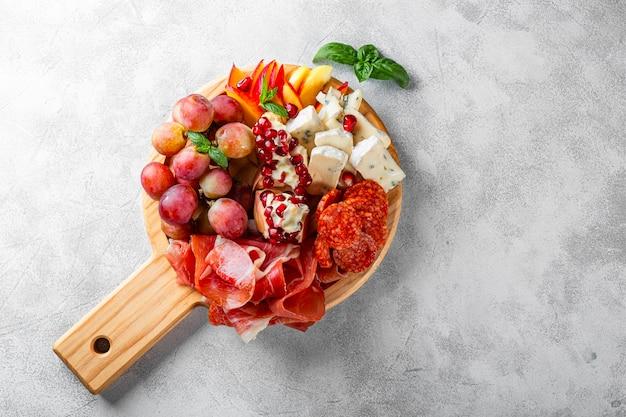Набор закусок для вина, хамона, пепперони, сыра, винограда, персика на виде сверху деревянной доски.