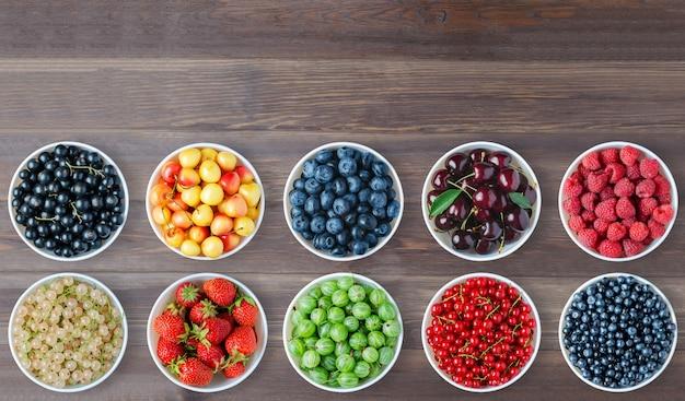 Набор ягод в круглых тарелках. коричневый деревянный фон. скопируйте пространство.