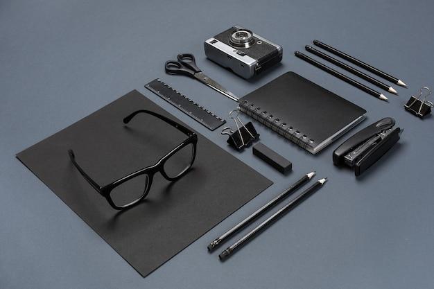 Набор черных офисных принадлежностей, очков и старой камеры на сером фоне. плоская планировка. натюрморт. макет