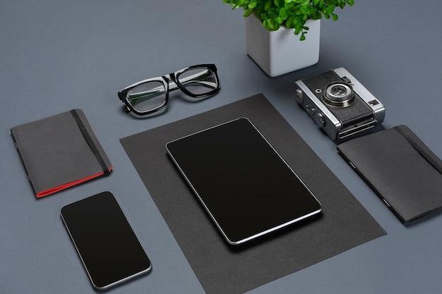Набор черных офисных принадлежностей, очков, зеленого цветка и умных на сером фоне. плоская планировка. натюрморт. макет