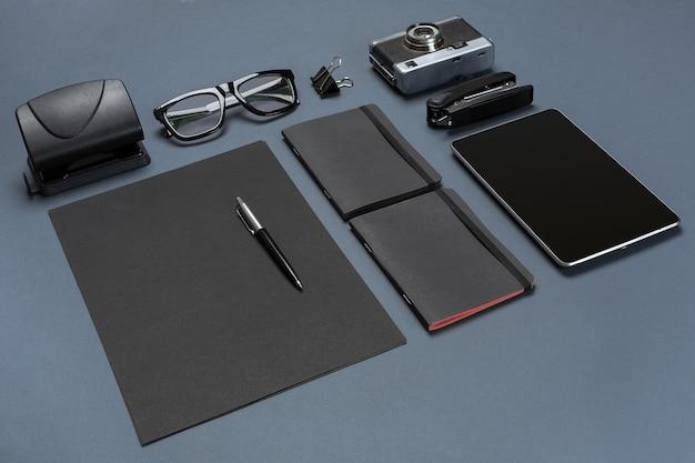 Набор черных офисных принадлежностей, очков, старой камеры и планшета на сером фоне. плоская планировка. натюрморт. макет