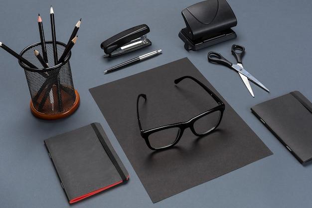 Набор черных офисных принадлежностей, очков на сером фоне. плоская планировка. натюрморт. макет