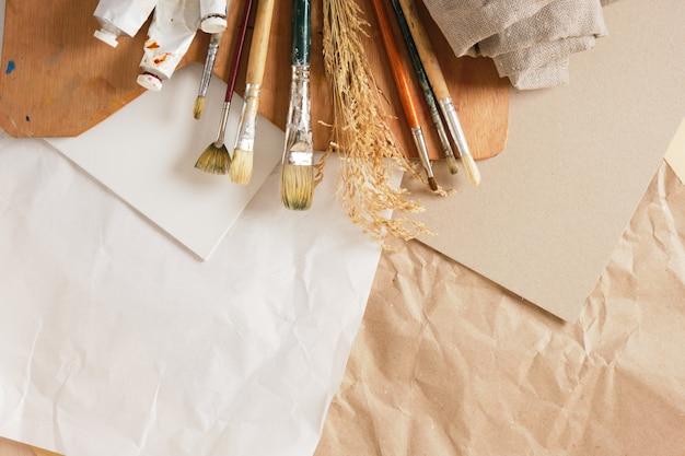 Набор кистей, деревянная палитра, белый холст на картоне и бумага на льняном фоне, концепция мастерской художника.