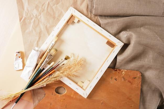 Набор кистей, краски в тубах, деревянная палитра, белый холст на подрамнике, бумага и белье на столе, концепция мастерской художника вид сверху