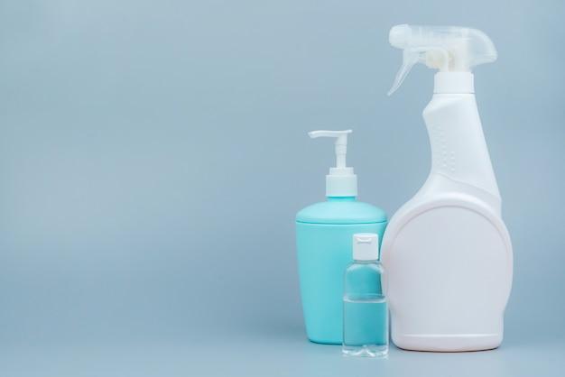 灰色の背景に一連の洗浄および消毒製品。テキストのためのスペースのクローズアップ。コロナウイルスの予防