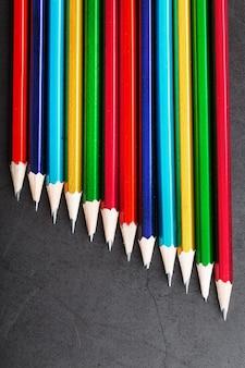 질감 있는 어두운 배경에 다채로운 연필 세트