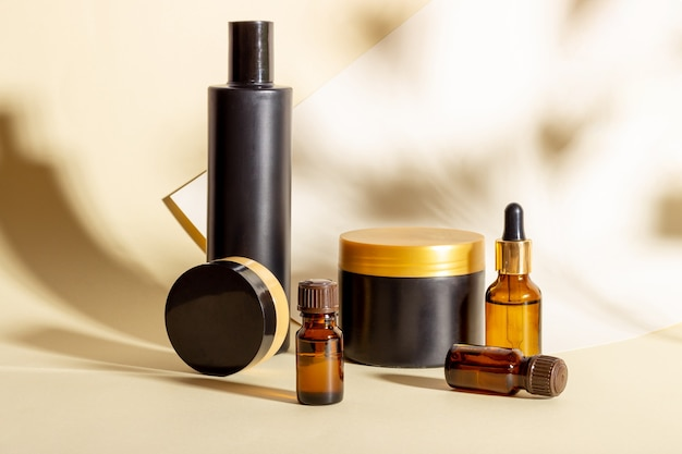 Набор косметических средств темного цвета на бежевом фоне с жесткими тенями. натуральная органическая косметика