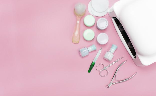 ピンクの背景にマニキュアとペディキュアの化粧品ツールのセット。ジェルポリッシュ、ネイルファイル、クリッパー、ランプの上面。テキストのための場所を持つカードの構成