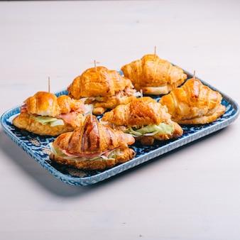 Набор круассанов и бутербродов с различными начинками, сыром, пармской ветчиной и салатом.