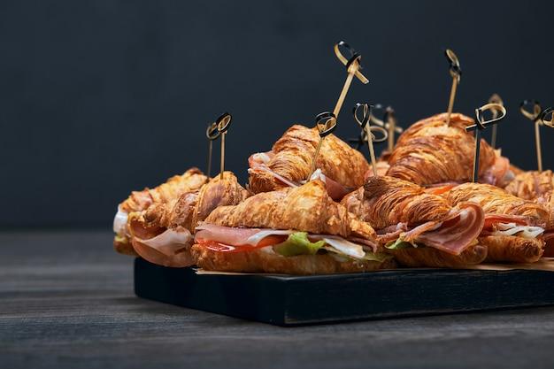 Набор круассанов и бутербродов с различными начинками, сыра, пармской ветчины, моцареллы и помидоров. фастфуд патерн