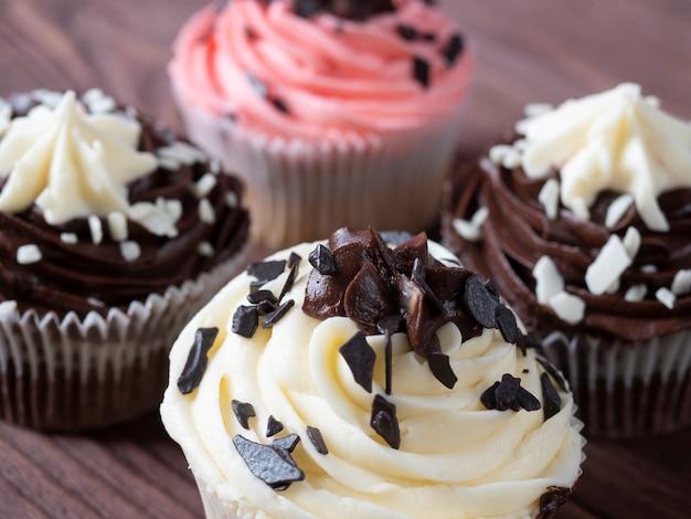 木製の背景においしくて甘いチョコレートカップケーキのセットです。高カロリーデザート、セレクティブフォーカス