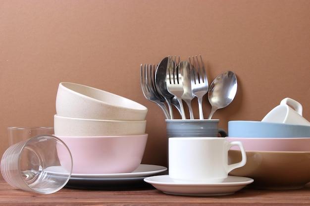 Набор посуды и кухонной утвари на цветном фоне
