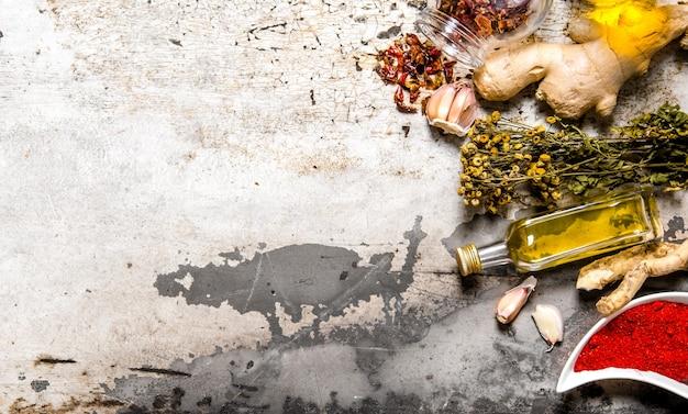 オリーブオイルと乾燥スパイスとハーブのセット。素朴な背景に。テキスト用の空き容量。上面図