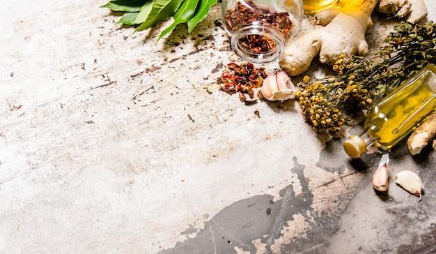 オリーブオイルと乾燥スパイスとハーブのセット。素朴な背景に。テキスト用の空き容量。