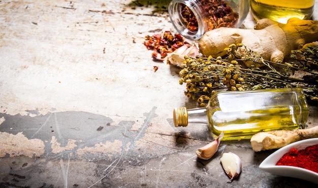 Набор сушеных специй и трав с оливковым маслом. на деревенском фоне. свободное место для текста.