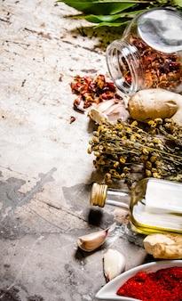 オリーブオイルと乾燥スパイスとハーブのセット。素朴な背景に。