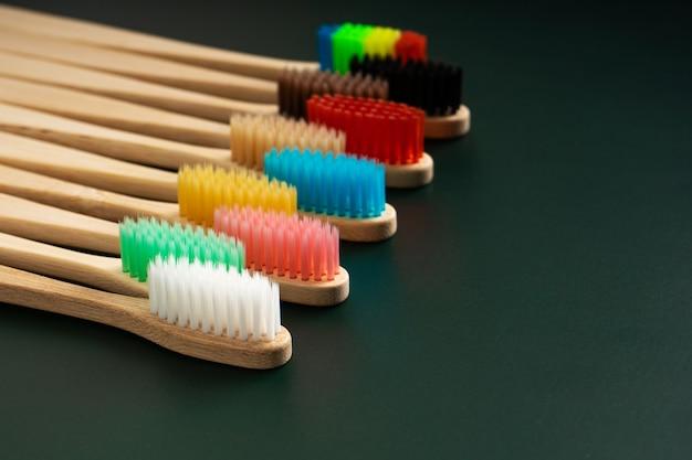 Набор экологически чистых антибактериальных зубных щеток из бамбуковой древесины на темно-зеленом фоне.