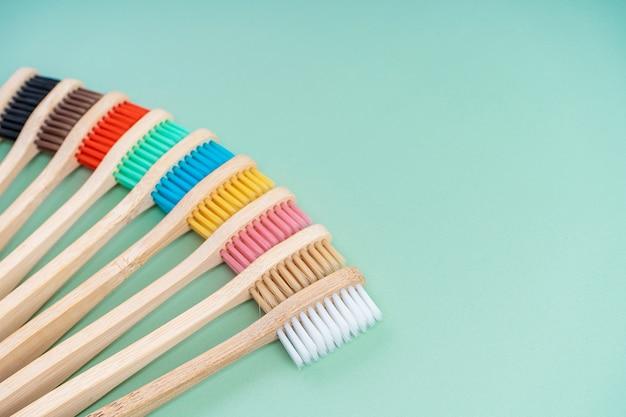 Набор экологически чистых антибактериальных зубных щеток из древесины бамбука на светло-зеленом фоне.