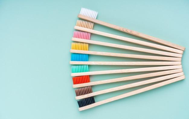 Набор экологически чистых антибактериальных зубных щеток из бамбукового дерева на светло-зеленой поверхности.