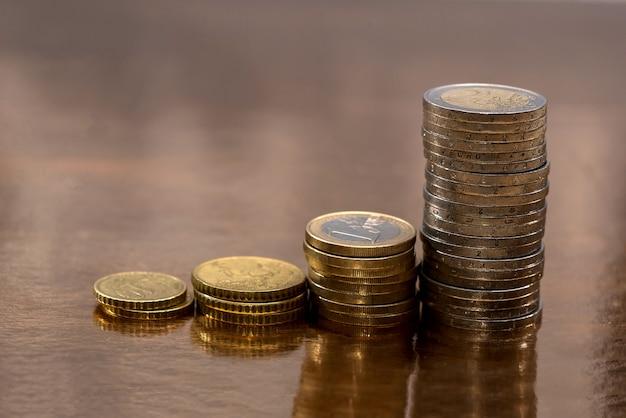 金色の背景に割り当てられたユーロ硬貨のセット