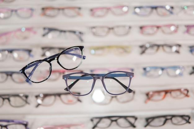 Набор очков, аккуратно разложенный в витрине для очков в офтальмологической клинике