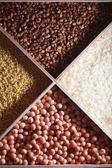 穀物シリアルのセット。米、そば、モロコシを木製のトレイに入れます。シリアルの食料品セット。穀物の輸入。