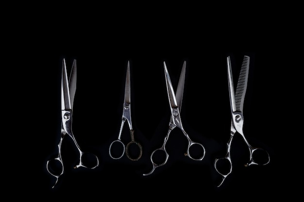 Набор инструментов для стрижки волос на черном фоне для парикмахерской бороды салона
